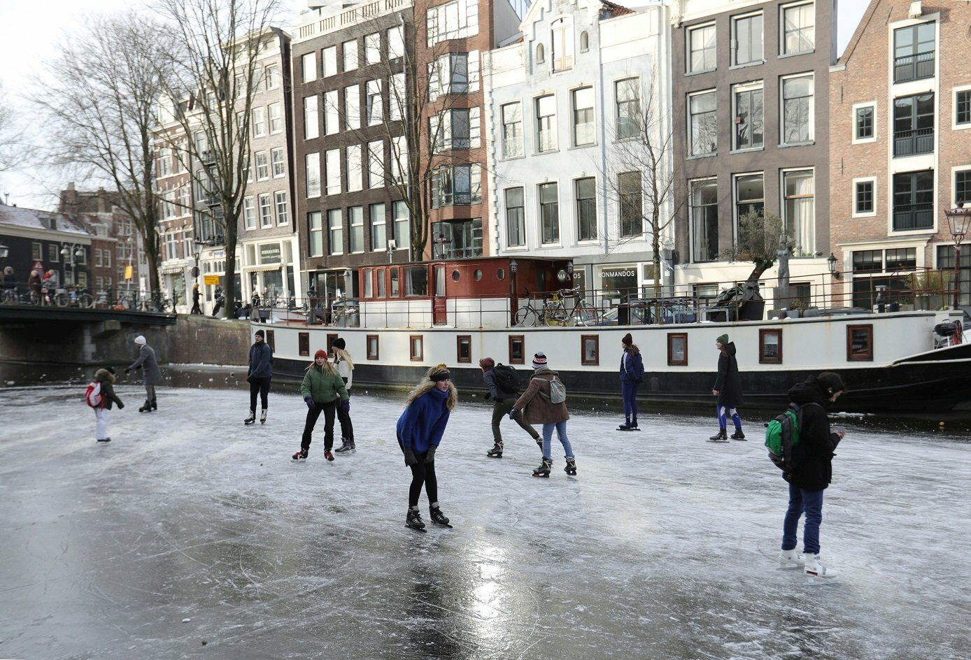 People ice skate during a cold snap across the country at the Prinsengracht in Amsterdam, Netherlands February 14, 2021.