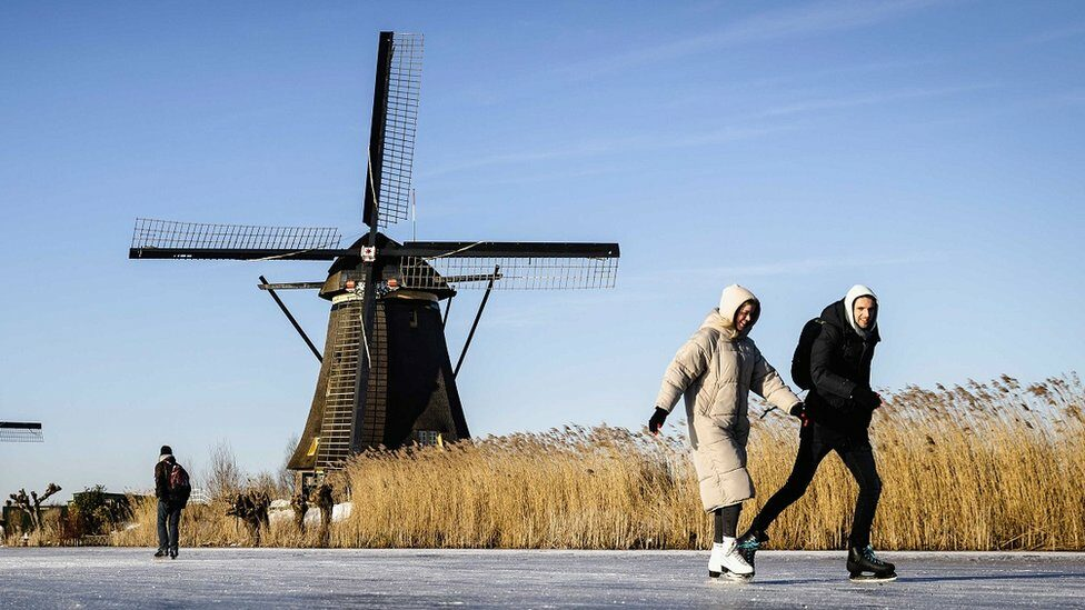 Skaters on the ice pass the windmills in Kinderdijk, The Netherlands, 13 February 2021.