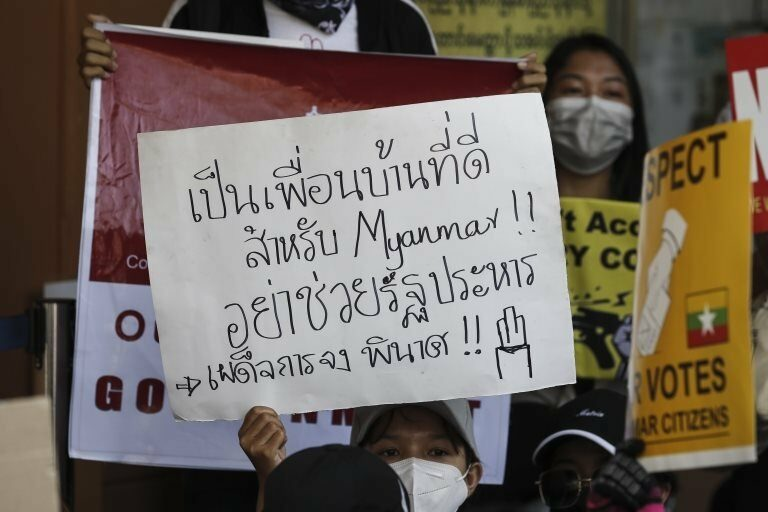 """A demonstrator holds a placard reading """"A good neighbour will not support a military coup"""" during a protest against the Myanmar military coup, outside the Embassy of Thailand in Yangon, Myanmar, 24 February 2021."""