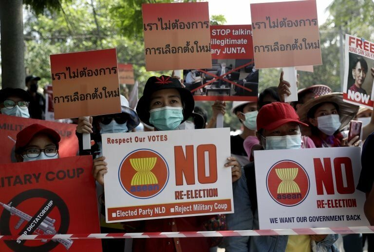 """Demonstrators hold placards reading """"We don""""t need re-election"""" during a protest against the military coup, near the Embassy of Thailand in Yangon, Myanmar, 26 February 2021"""
