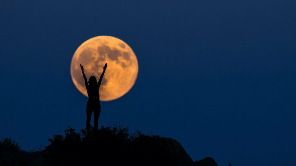 An orange full moon, with a woman in front of it, arms in the air.