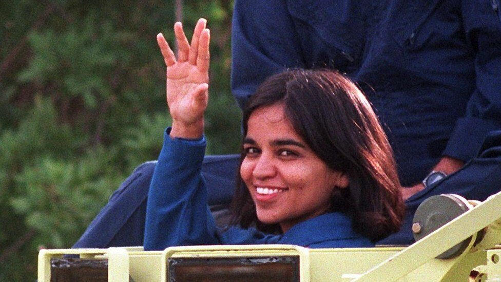 US space shuttle Columbia crewmember Doctor Kalpana Chawla, native of Karnal India, waves to the media 03 November from the drivers seat of an M-113 personnel carrier after a stint at driving the escape vehicle during crew training at Kennedy Space Center.