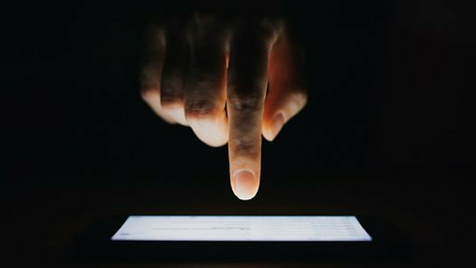 Finger pointing at mobile phone screen