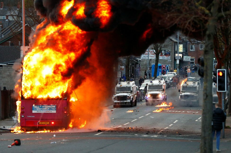 A bus burns on a street in west Belfast