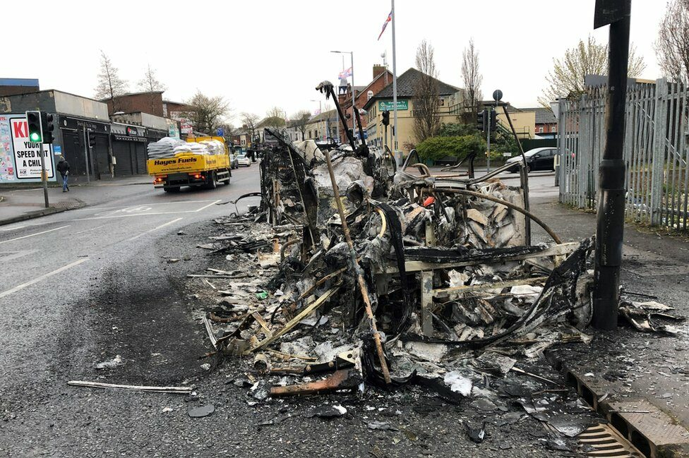 The burnt wreckage of a bus that was set on fire during rioting in west Belfast