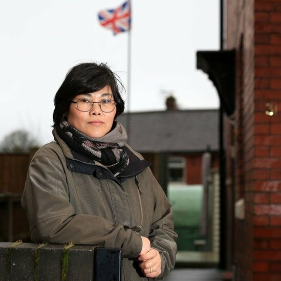 Jihyun Park stands in front of a house with a union flag flying in the background