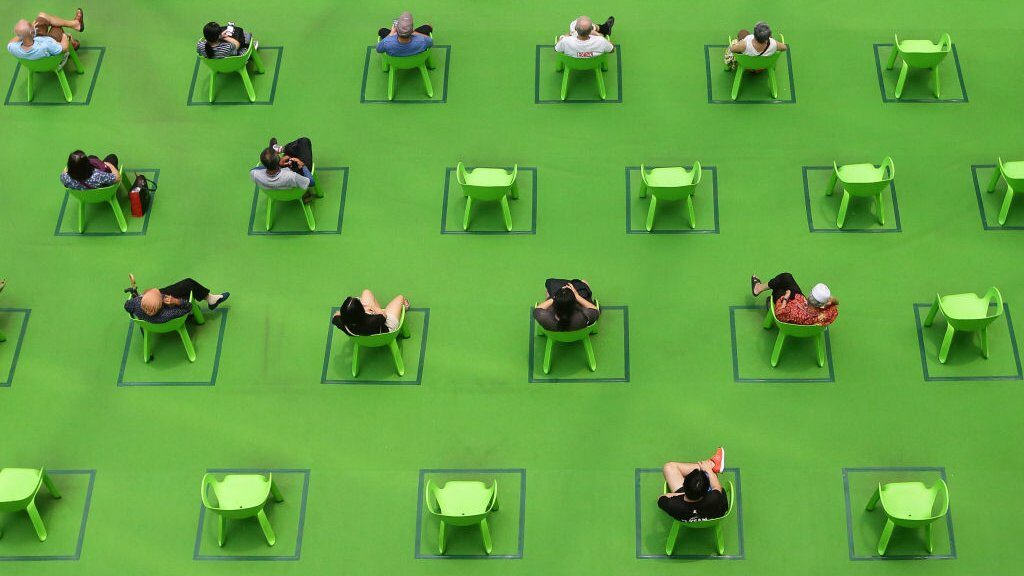 People sit on chairs marked out to maintain social distancing amid the COVID-19 pandemic on 19 March 2021 in Singapore