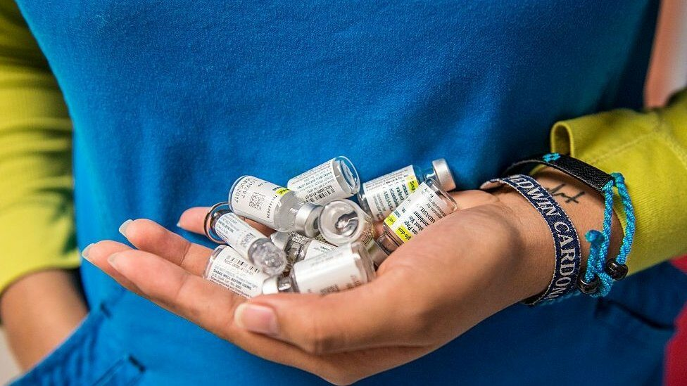 A nurse carries empty vials of HPV vaccine