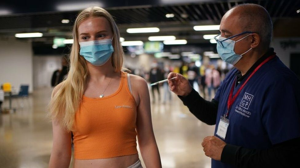 """Maisie Ayres, aged 18, receives a Pfizer BioNTech COVID-19 vaccine at an NHS Vaccination Clinic at Tottenham Hotspur""""s stadium in north London."""