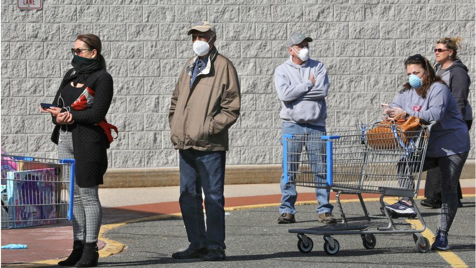Shoppers in a line with masks on