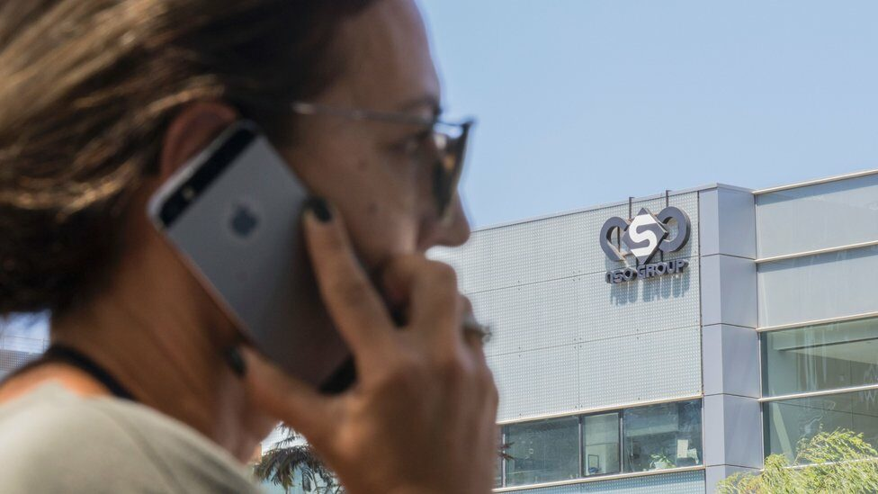 An Israeli woman uses her iPhone in front of the building housing the Israeli NSO group, on August 28, 2016, in Herzliya, near Tel Aviv.