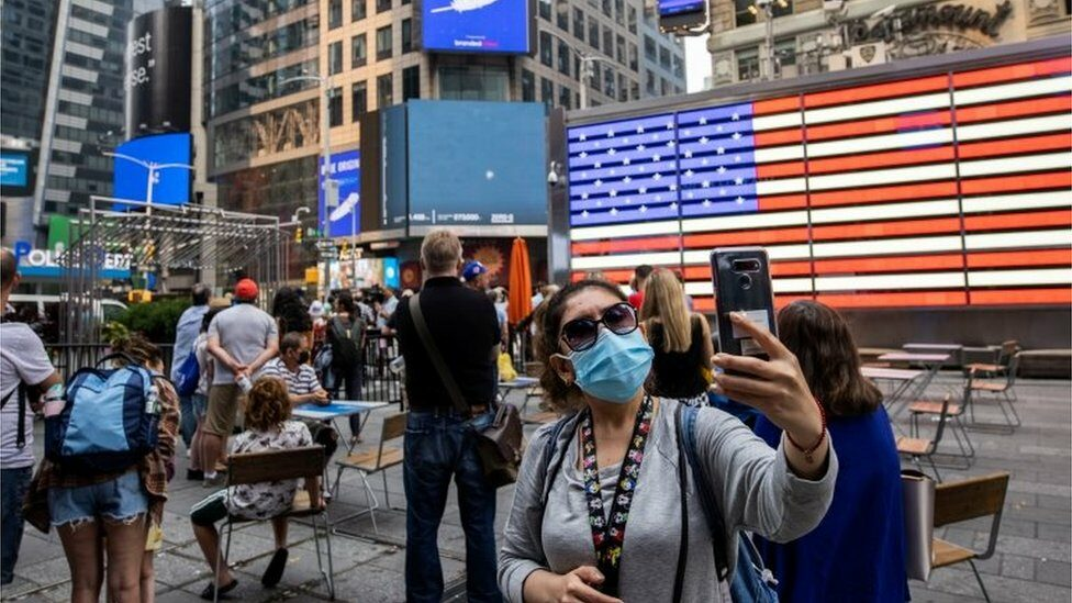 """People watch the launch of Blue Origin""""s inaugural flight to the edge of space, on a screen in Times Square in New York"""