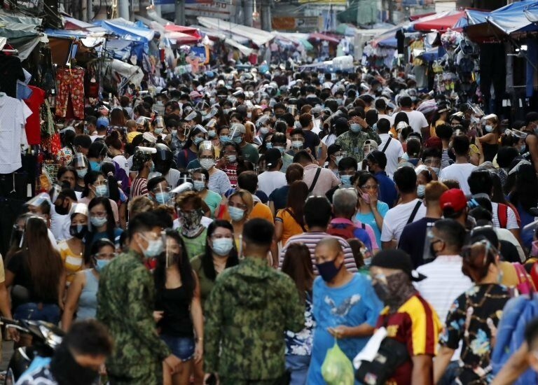 A crowd of shoppers next to makeshift stores to choose from an assortment of items sold at bargain price along a road in Manila, Philippines, 23 December 2020