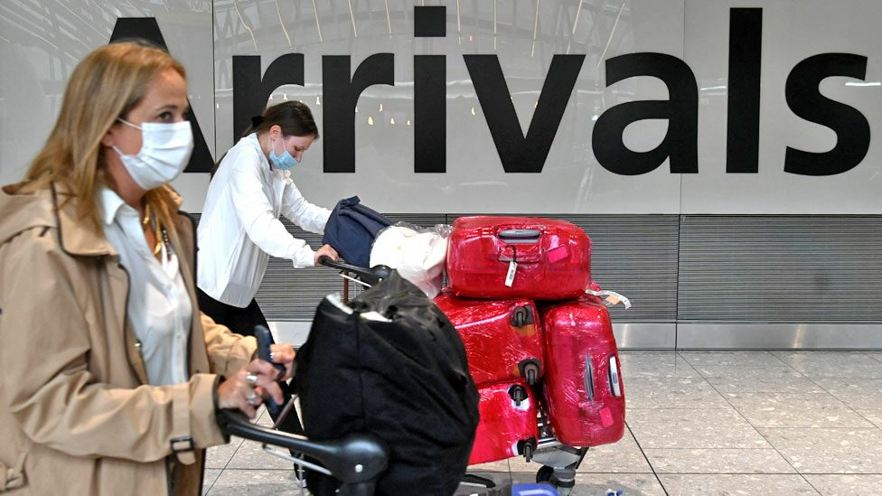 Passengers push their luggage trolleys on arrival in Terminal 5 at Heathrow airport in London in June 2021