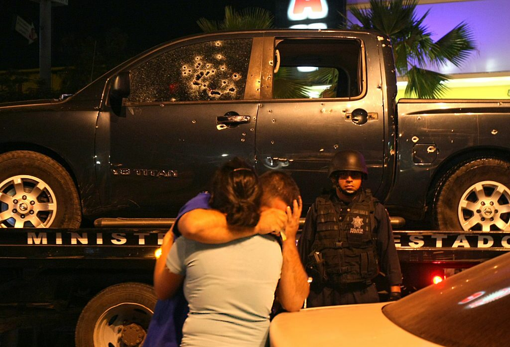 A policeman is consoled by his wife after a fatal shootout between narcos and police in Culiacan.