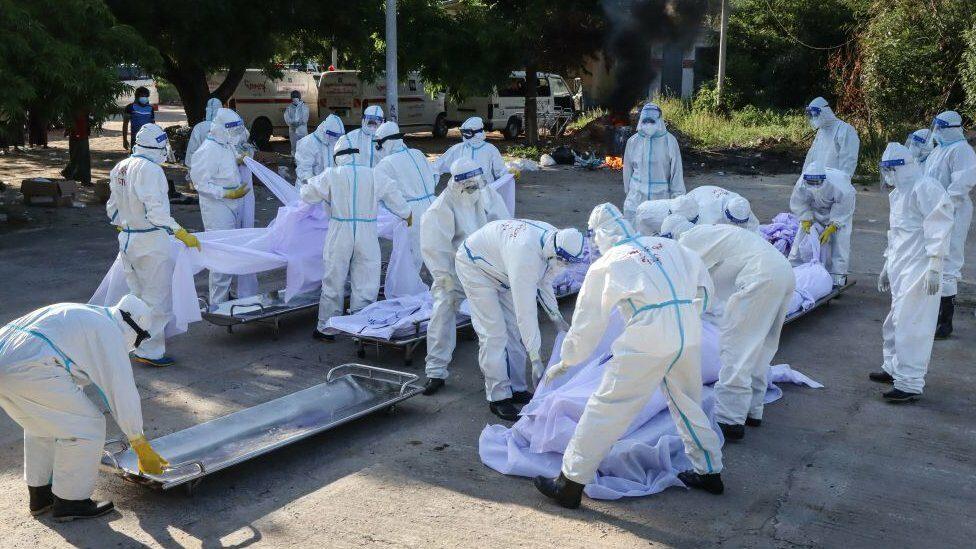 อาสาสมัครในชุดพีพีอี จัดการศพของผู้เสียชีวิตจากโควิดในเมืองมัณฑะเลย์