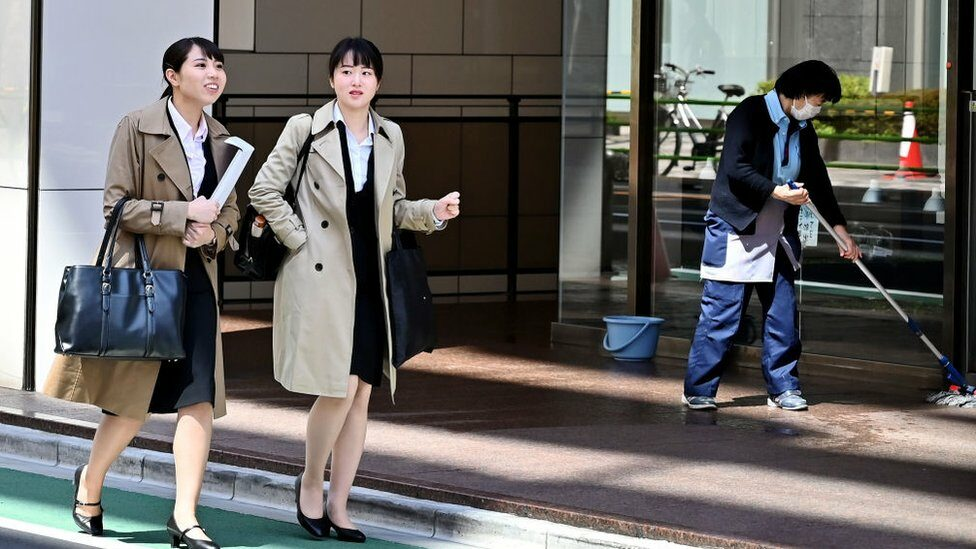 Women walk past a cleaner in Tokyo's Ginza district on April 3, 2019