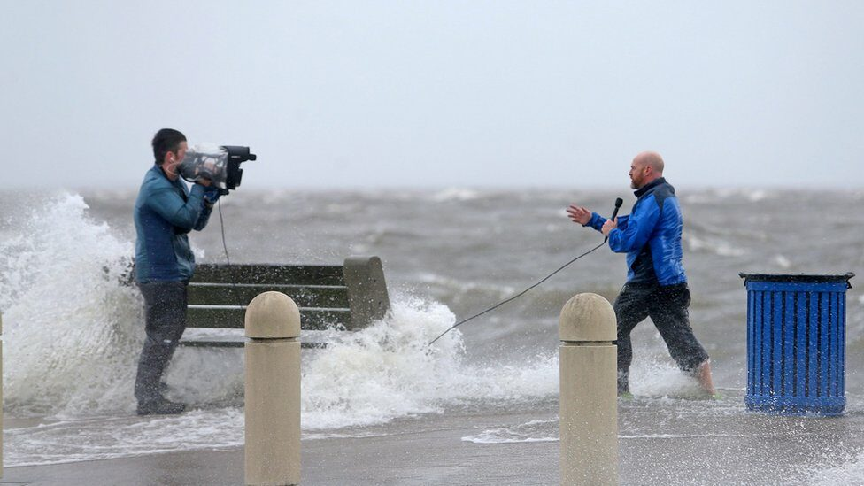 A news crew films as the storm surge pushes water from Lake Pontchartrain