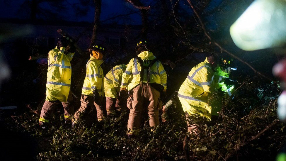 Firefighters clear trees from the road in Bourg, southern Louisiana