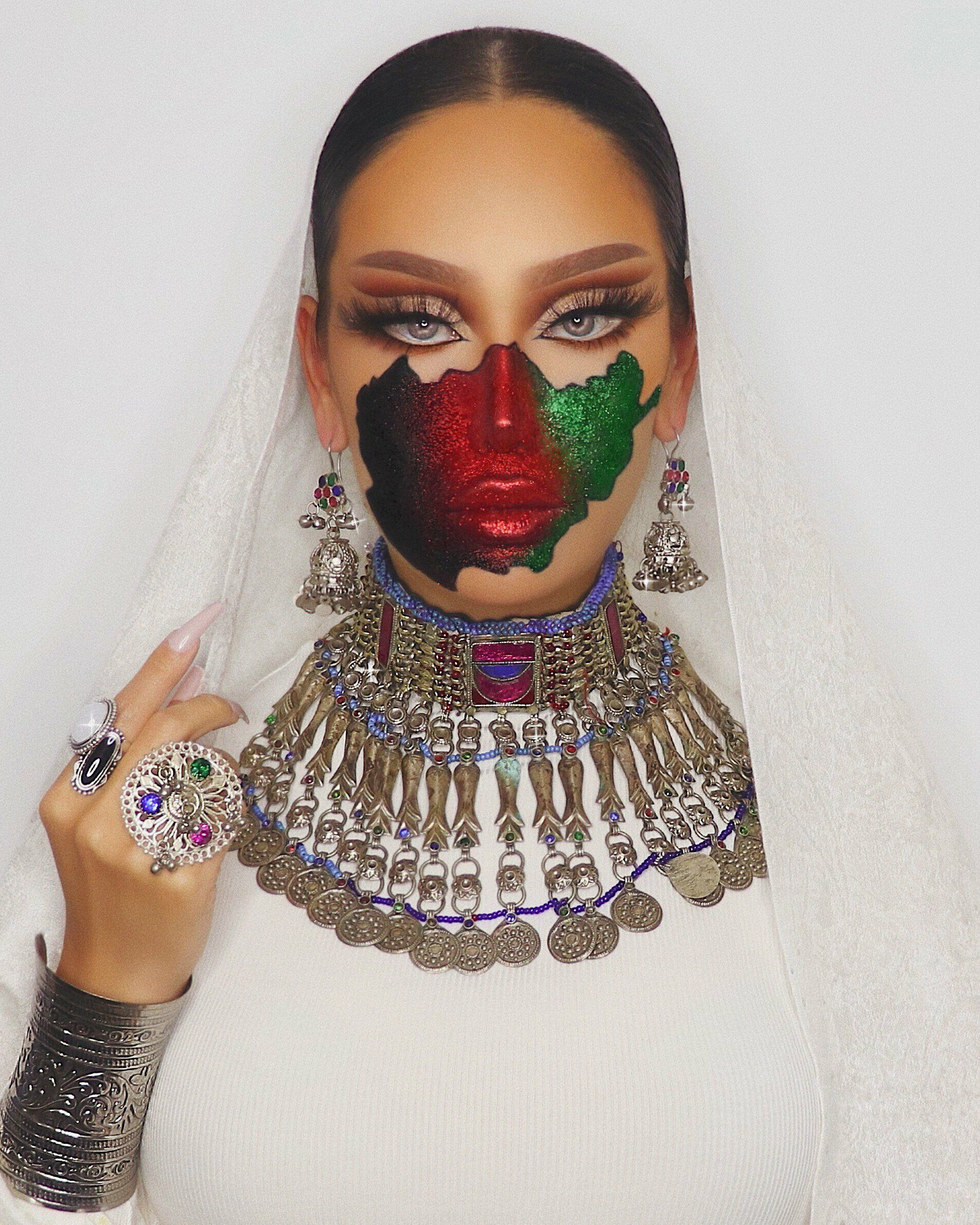 An Afghan female model with make-up of the Afghanistan flag painted on her face