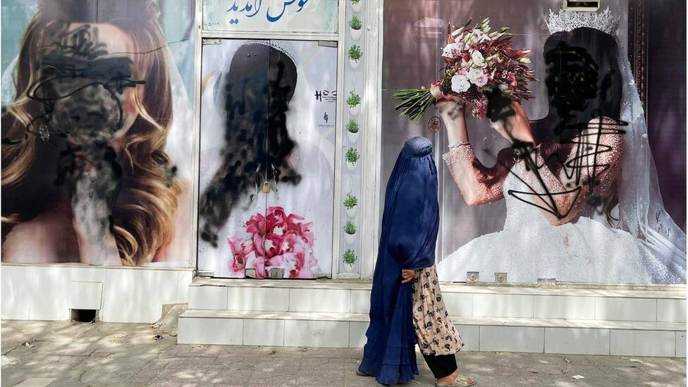 A woman in a burkha walks past a shop where posters of models are covered over