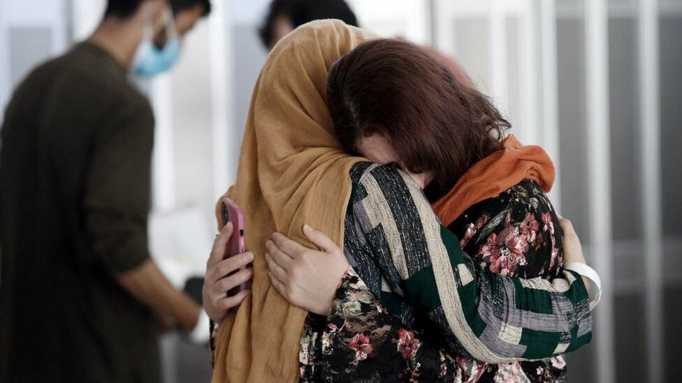 An Afghan woman greets her relative at the Vienna airport