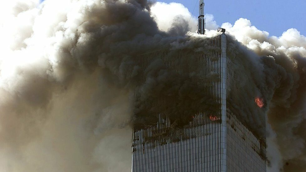The north tower of the World Trade Center burns after being hit by a hijacked plane on 11 September 2001